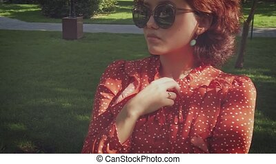 Slow motion shot of young asian woman in retro sunglasses and red summer dress moving in front of green lawn of city park.
