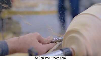 Carpentry, craftsmanship, design, manufacturing concept. Close up view - professional man carpenter using skew chisel for shaping piece of wood on woodturning lathe at workshop- super slow motion