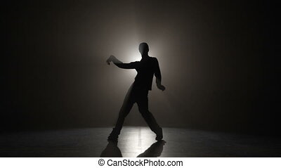 Slow motion silhouette of a man wearing cap and performing electric dance wave moves on a dark stage before the concert
