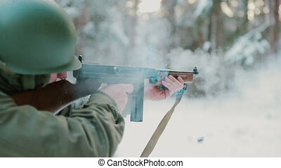 Slow Motion Soldier dressed as USA Infantry Soldier Of World War II Aiming And Shooting From Submachine Gun Weapon. American Soldier In Attack In Winter Forest