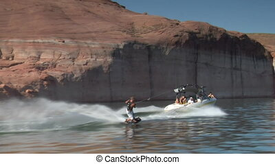 slow-motion speedboat pulls wake boarder Lake Powell Utah...