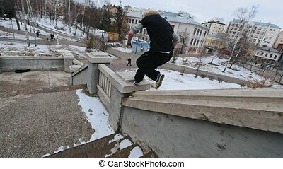 Slow motion steadicam shot of a young athlete performing acrobatics in the marble staircase at winter city