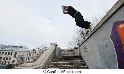 Slow motion steadicam shot of a young athlete performing acrobatics outdoor in the winter city