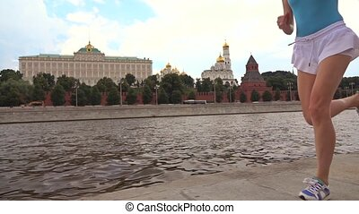 Slow motion steadicam shot of athletic brunette girl runner against Moscow Kremlin 240 fps