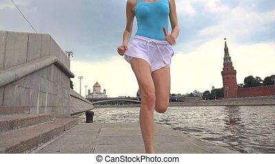 Slow motion steadicam shot of athletic brunette girl jogger against Moscow Kremlin 240 fps