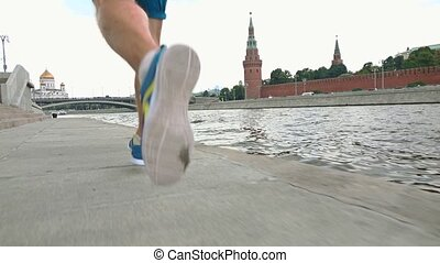 Slow motion steadicam shot of athletic runner legs against Moscow Kremlin, Russia. Shot at 120 fps