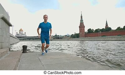 Slow motion steadicam video of athletic caucasian runner against Moscow Kremlin, Russia. Shot at 120 fps