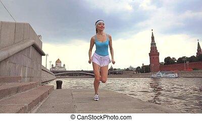 Slow motion steadicam video of a beautiful girl runner against Moscow Kremlin 240 fps