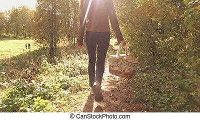 Slow motion steadicam video of a young brunette woman walking through autumn woods holding a basket
