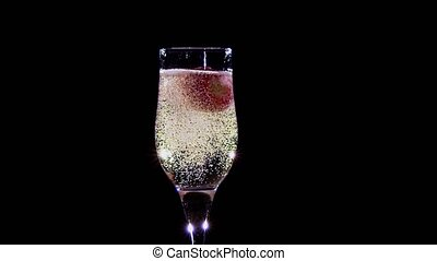 Slow motion. Strawberry in glass with champagne wine covered bubbles