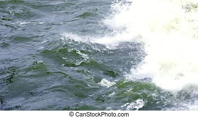 SLOW MOTION: Strong waves roll on the stones. The waves hit hard on the rocks. Spray fly in different directions. Cold wind is blowing. A cloudy autumn day at sea