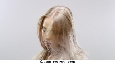 Slow motion studio portrait of a blonde woman's hair blowing...