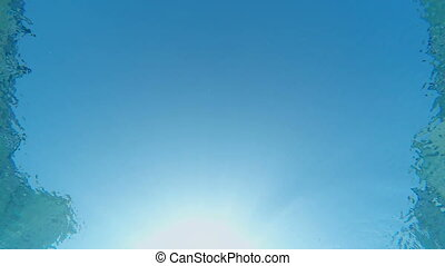 SLOW MOTION: Sun and sky through the blue water of swimming pool underwater shot