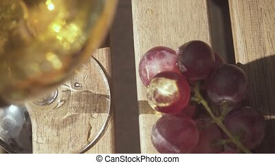 Slow motion sunbeam on a bunch of grapes on a table