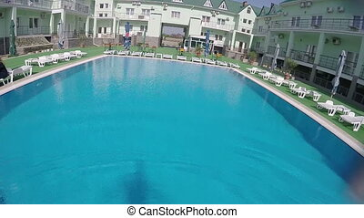 SLOW MOTION: Swimmer jumping into blue water of outdoor hotel pool and swimming underwater PoV