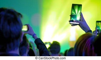 Slow motion: teenagers hands taking photo or recording video of live music concert with smartphone. Bright colorful stage lighting. Nightlife, technology, photography, entertainment concept
