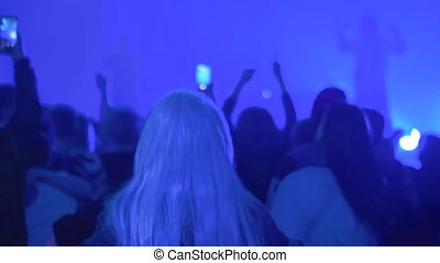 Slow motion: teenagers partying, cheering, raising hands up and jumping at rock concert in front of stage of nightclub. Bright colorful stage lighting. Nightlife and entertainment concept