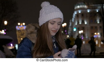 Slow motion. The girl writes sms on the smartphone. In the...