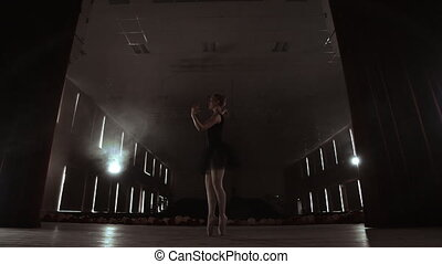 Slow motion: the prima ballerina in a black dress performs rotations and graceful dance moves. The camera moves on gimbal.