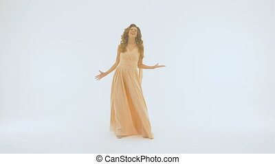 Slow motion The singer in a long beautiful dress sings on the background of a white wall. She spreads her hands in different directions.