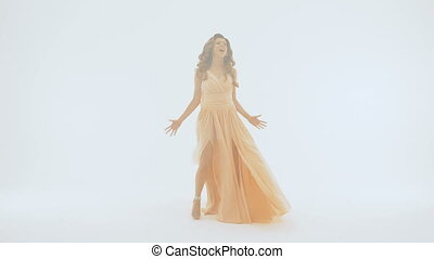 The singer in a long beautiful dress sings on the background of a white wall.