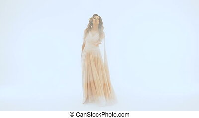 Slow motion The singer in a long beautiful dress sings on the background of a white wall. She spreads her hands in different directions