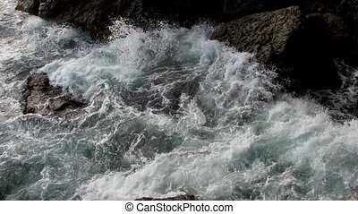 Slow motion The surf is hitting coast stones and make the splashes and foam jump up Lush sea colors and patterns created by nature energy