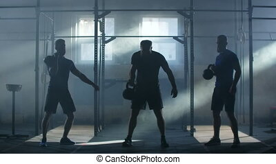 Slow motion: Three Friends fitness athletes men training muscular bodybuilders using kettlebell weights doing intense strength exercise friends enjoying weightlifting together in gym.