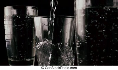 Slow motion. Three glasses on a black background with lemon...