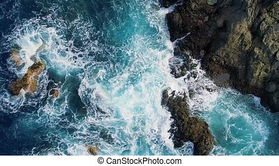 slow motion top down view of waves and clifs - top down view...