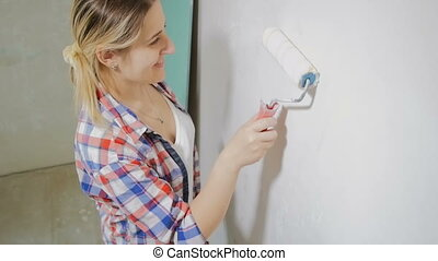 Slow motion top view footage of smiling woman painting wall with roller