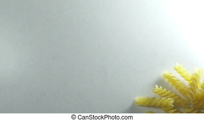 SLOW MOTION-TOP VIEW: Many of noodles fall on a white table
