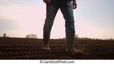 Slow motion tractor drivers boots walk across a plowed field at sunset after a working day