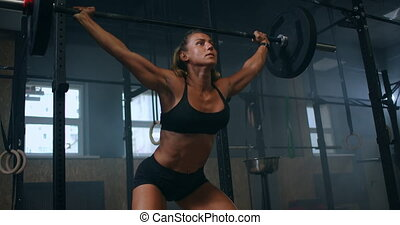 Slow motion: Training squats with barbells over head. Muscular female lifting barbell over head training shoulders at gym. Confident fitness woman practicing force workout with heavy equipment. High quality 4k footage