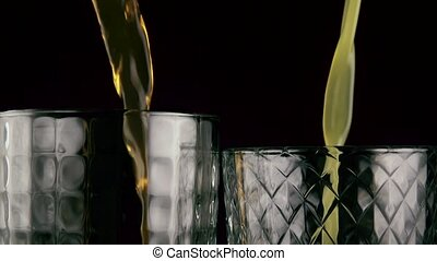 Slow motion. Two glasses filled with orange drinks