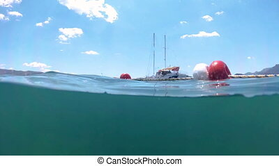 Slow motion underwater footage moored yachts in sea at...