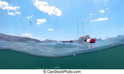 Slow motion underwater footage of moored yachts and life...