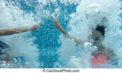 Slow motion underwater footage of two girls holding hands...