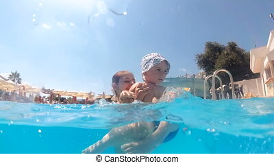 Slow motion underwater video of cheerful toddler boy playing with mother in swimming pool at aquapark