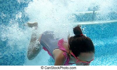 Slow motion underwater video of teenage girl in striped...