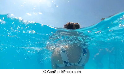 Slow motion underwater video of young mother holding and...