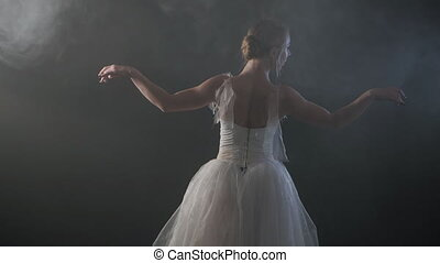 SLOW MOTION. unrecognizable beautiful ballerina performing on dark smoke stage. Blonde woman in white ballet dress tutu dancing with hands