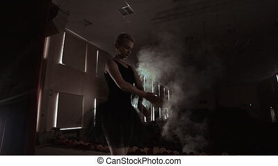 SLOW MOTION. unrecognizable beautiful ballerina performing on dark smoke stage. Blonde woman with hair in black. Ballet dress dancing with hands.