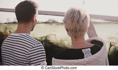 Slow motion unrecognizable man and woman stand near big fish...