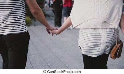 Slow motion unrecognizable man and woman walk holding hands...