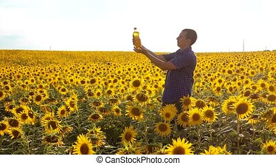 slow motion video. Man farmer hand hold bottle of sunflower...