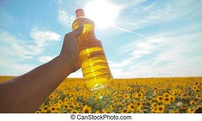 slow motion video. Man farmer hand hold bottle of sunflower...