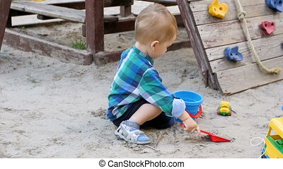 Slow motion video of adorable toddler boy playing in sandbox...
