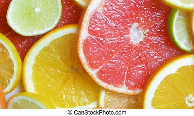 Slow motion video of assortment of fresh citrus fruits lying...