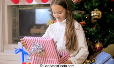 Slow motion video of beautiful brunette girl taking grey kitten out of Christmas gift box